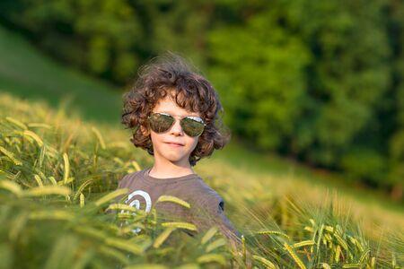 Kisfiú játszik a benyújtott napnyugta, napszemüveg Stock fotó