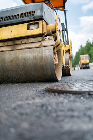 construction vibroroller: Road roller flattening new asphalt.