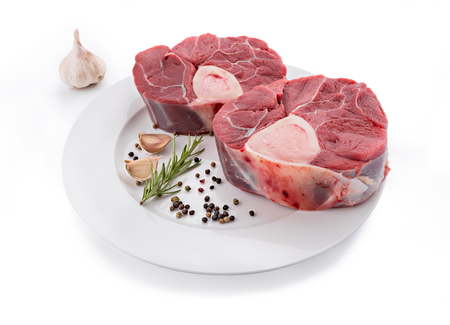 Raw fresh cross cut veal shank and seasonings for making Osso Buco
