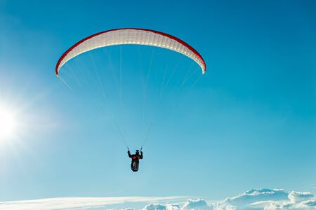 away from it all: Paraglider flying over the clouds - into the sun Stock Photo