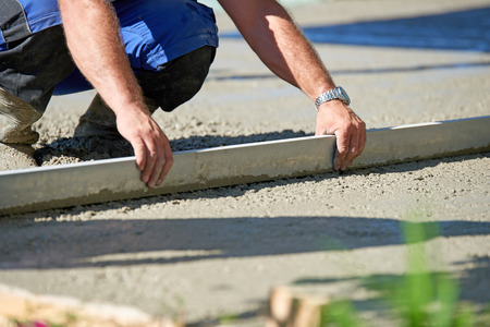 Worker screeding cement floor with screed Stockfoto