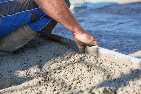 rennovation: Worker screeding cement floor with screed Stock Photo