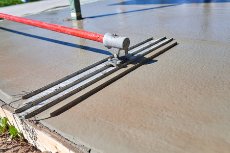 Leveling concrete with bull float, mason hands spreading poured concrete