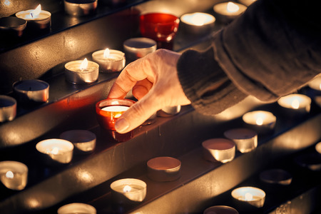 Lighting a candle for someone - Votive church candles in rows 스톡 콘텐츠