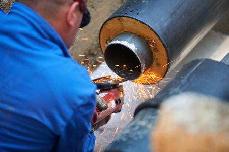 Electric wheel grinding on steel pipe� Metal worker grinding metal of pipeline