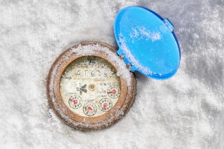 Broken glass on water meter clock in the snow- below zero