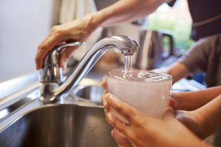 Cerca de las manos de la mujer y los niños, vertiendo un vaso de agua fresca del grifo en la cocina Foto de archivo