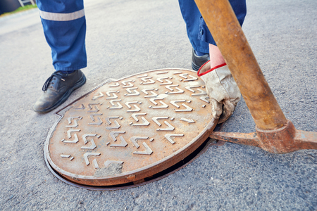 Emptying septic tank, cleaning the sewers. Worker opens a manhole in to descend underground.