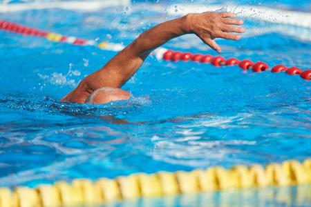 Aktives Seniorenschwimmen. Älterer Mann, der in einem Freibad schwimmt.