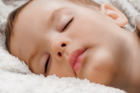 Portrait of asleep child on white fluffy plaid