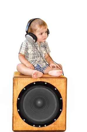 Portrait of child in earpiecess sitting on subwoofer on a white background Stock Photo