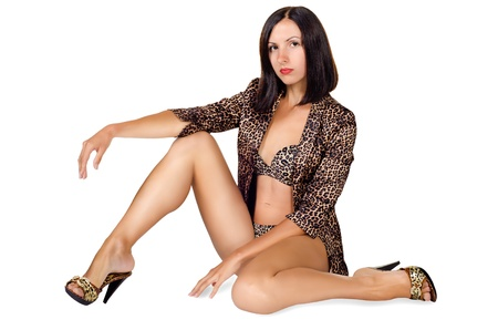 a girl in leopard clothes sits on a white background