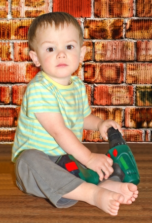 a boy sits with a drill on a background a brick wall