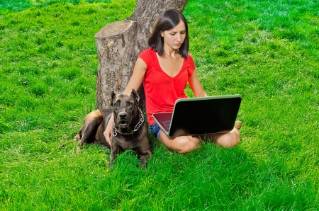 a girl with a notebook sitting under a tree together with a dog Stock Photo - 15921611