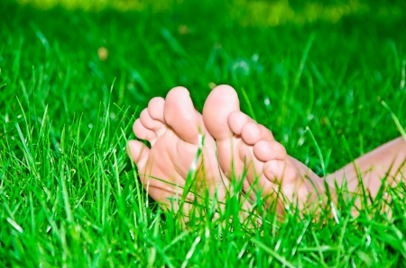 womanish legs are in a green grass Stock Photo