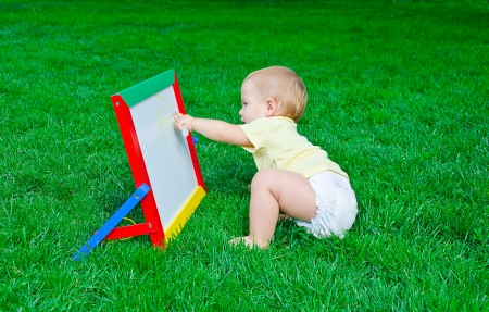 beautiful little boy draws a marker on a board sitting on a lawn photo
