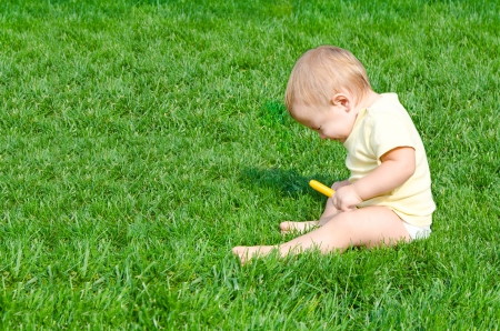 А pretty little boy sneezes sitting on a grass photo