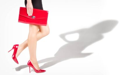 Beautiful slender womanish feet are in red shoes, shade from a model in complete growth photo