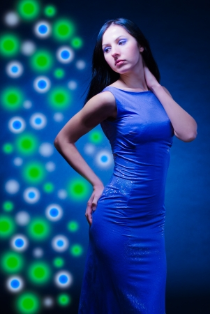Beautiful slender woman is in a dark blue evening dress Stock Photo - 16985577