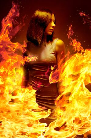 Young beautiful girl is in blazing flame Stock Photo