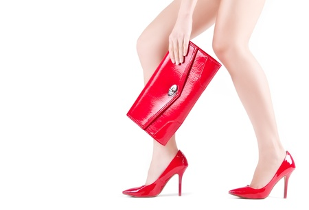 Beautiful slender womanish feet in red shoes and mini bag Stock Photo