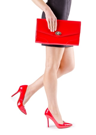 Slender beautiful womanish feet in red shoes and mini bag Stockfoto
