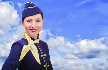 hotesse de l air: Belle jeune hôtesse souriante en uniforme sur un fond de ciel