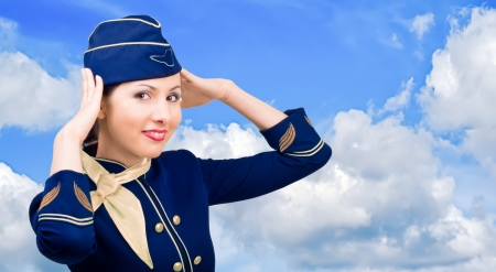 Beautiful smiling stewardess in uniform on a background sky Stock Photo - 17425262