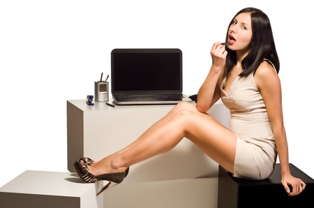 Beautiful young girl paints her lips with lipstick sitting at the computer in the office environment with your feet raised on a white background Stock Photo - 17502582