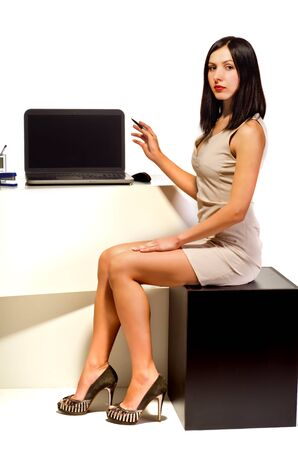 Young beautiful girl sitting at the computer in the office environment and shows up on the monitor Stock Photo - 17502581