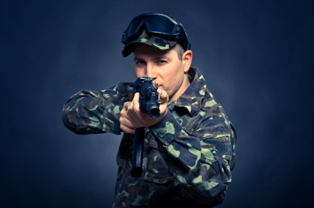 Soldier aiming a machine gun on a blue background with a focus on the barrel machine photo