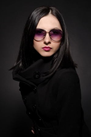 Portrait of a beautiful young woman in sunglasses on black background Stock Photo