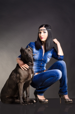 Beautiful woman in denim clothes sitting next to the dog photo