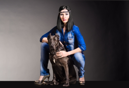 Beautiful woman in jeans clothes sitting next to the dog photo