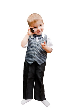 denote: Beautiful little boy talking on a mobile phone pointing