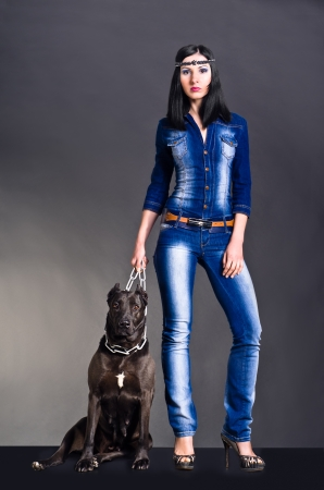 Beautiful young woman in jeans clothes  standing next to a dog photo