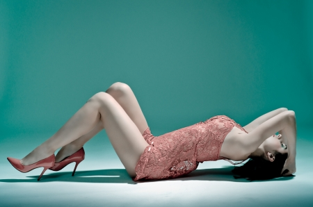Sexy graceful young woman lying on the floor in a lace nightie Stock Photo