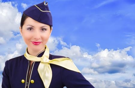 Bella azafata sonriente sobre un fondo de cielo photo
