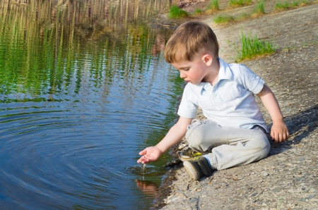 Small beautiful boy pours water from the palm on the river Stock Photo