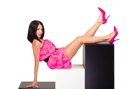 Sexual beautiful girl in pink dress with feet lifted up Stock Photo