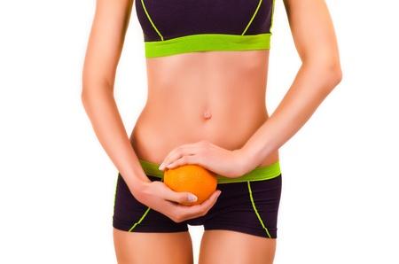 sportwear: Slim figure of woman in a sportwear with orange in a hands Stock Photo