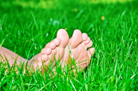 Female feet in green grass