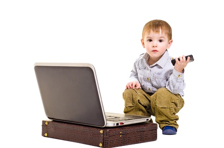 Cute boy with a mobile phone is sitting next to a laptop photo