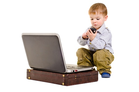 Cute small boy dials on a mobile phone while sitting next to laptop Stock Photo