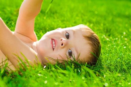 Portrait of little beautiful boy lying on the grass Stock Photo