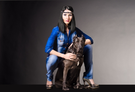 Beautiful woman in jeans clothes sitting next to pitbull Stock Photo