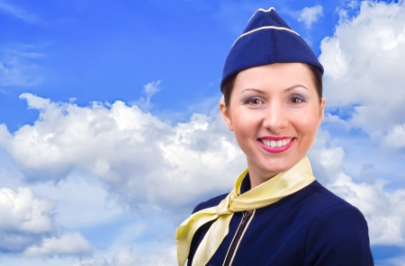 airline hostess: Beautiful smiling stewardess  on a background sky Stock Photo