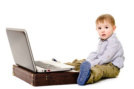 Beautiful little boy sitting on the floor with a laptop