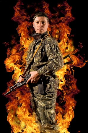 Soldier stands with a gun in his hand and safety glasses in a burning fire
