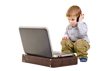 Cute boy speaks on a mobile phone looking at laptop photo